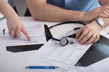dagvaarding: Roept papier op de tafel in het kantoor van arts Stockfoto