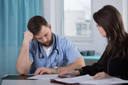 Physician who commit medical error talking with lawyer Foto de archivo