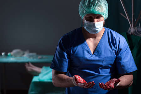 hand therapy: Young surgeon with bloody hands after operation