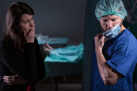Surgeon talking with woman about her husbands death Stock Photo