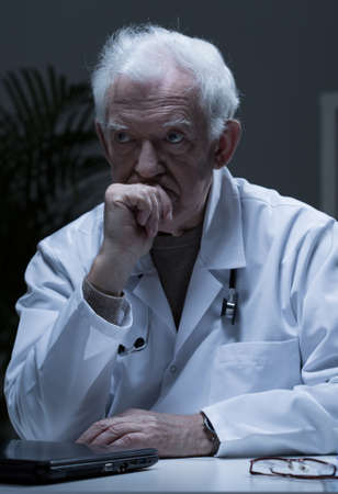 practiced: Thoughtful senior doctor sitting at the desk Stock Photo