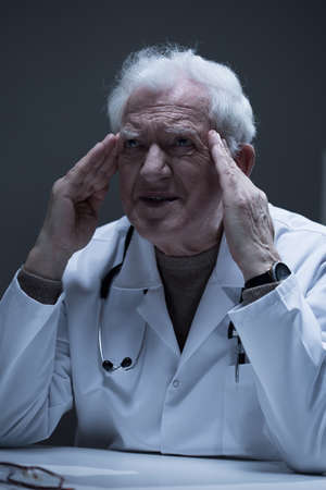 practitioner: Thoughtful senior practitioner having problems at work