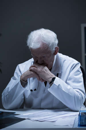 registrar: Aged male doctor thinking about medical problem