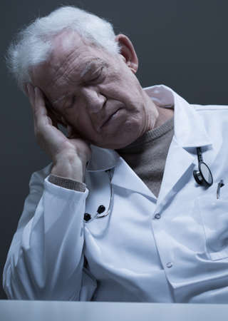 registrar: Male old doctor sleeping at the desk Stock Photo