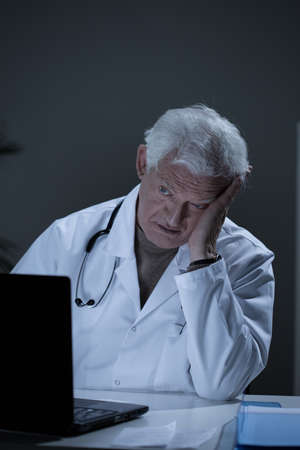 practitioner: Depressed aged practitioner working in his office