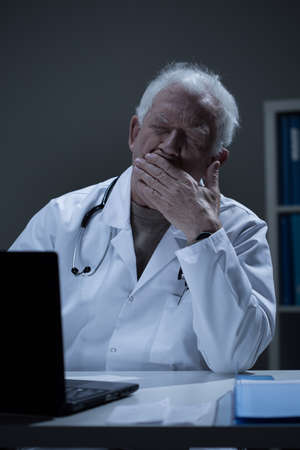 overworking: Overworked doctor sitting at the desk and yawning Stock Photo