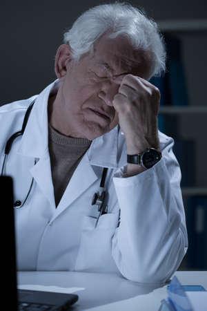 medic: Aged medic having sinus pain at work