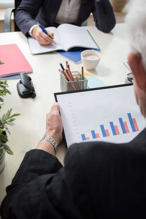 the latest: Elder experienced businessman checking the latest statistics