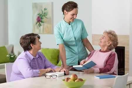 retirement homes: Two elderly women reading and talking to a smiling nurse Stock Photo