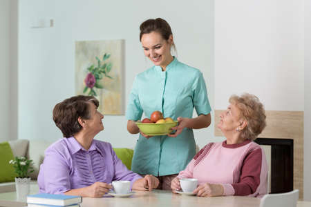 spare time: Two old women having tea and apples