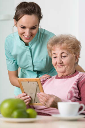 memorable: Old woman and her nurse looking at a sentimental photo