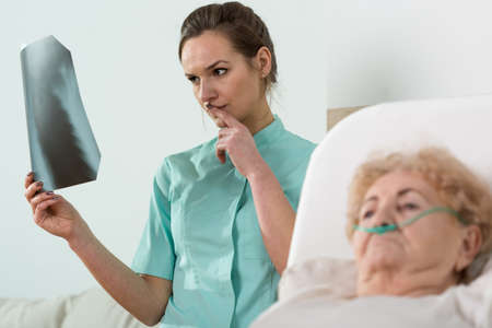 analysing: Nurse analysing an X-Ray of an elderly woman Stock Photo
