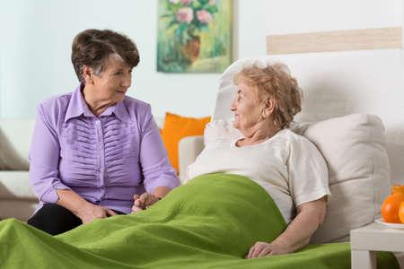chory: Kobieta odwiedzając jej chorego starszego znajomego