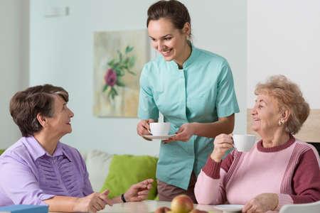 vejez feliz: Dos mujeres de edad y una enfermera tomando una taza de t�