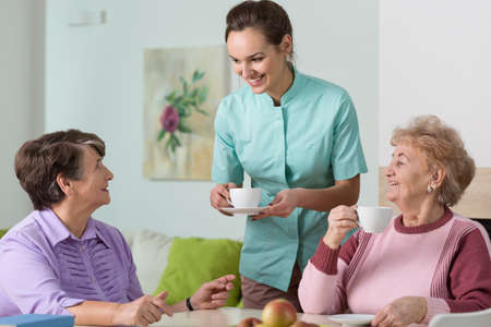 old: Two old women and a nurse having a cup of tea