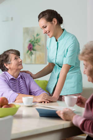 old age care: Young nurse taking care of elderly women