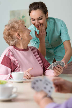 age care: Nurse whispering with an elderly playing cards