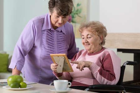 sentimental: Two elderly women smiling at a sentimental photo