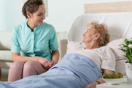 cama: Señora mayor en una cama de hospital y una enfermera joven