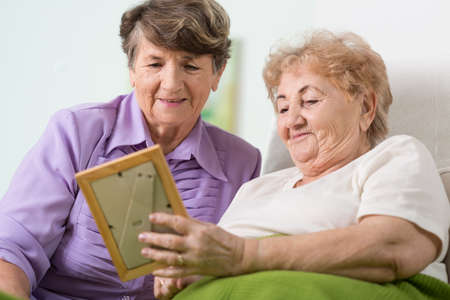 memorable: Elderly friends looking at a memorable picture together Stock Photo