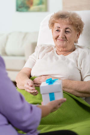 doctor holding gift: Woman giving her elderly and sick friend a present