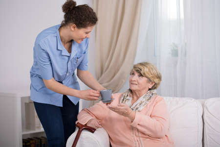 Young caregiver caring about elder lady at home Stock Photo