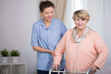 health care worker: Senior woman and supporting nurse at home Stock Photo