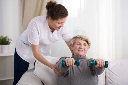 Old woman training with physiotherapist at home Stock Photo