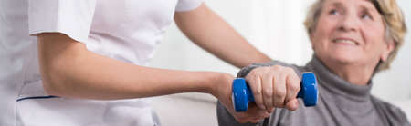 rehabilitation: Elder woman training with dumbbell supported by physiotherapist