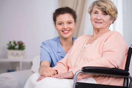 Smiling elder woman sitting on a wheelchair 写真素材
