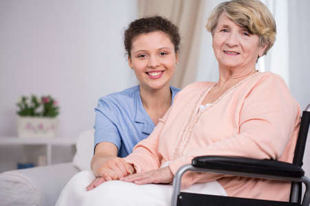 care at home: Smiling elder woman sitting on a wheelchair Stock Photo