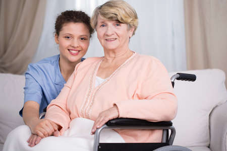 Disabled senior woman and smiling female carer