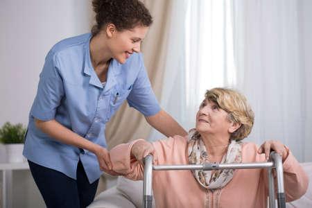 pielęgniarki: Starszy kobieta za pomocą balkonika i wspieranie pielęgniarki Zdjęcie Seryjne