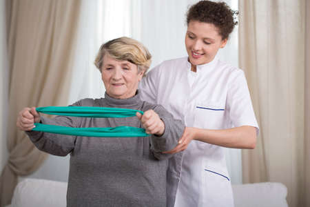 therapy room: Active elder lady training with exercise elastic band