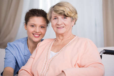 Senior woman and young nurse at home