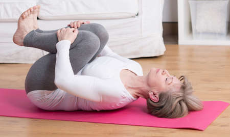 Beauty mature woman practicing pilates at home Stock Photo