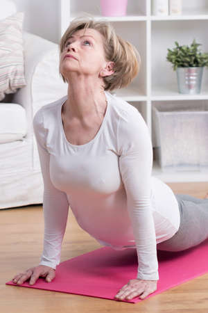 floor mat: Woman doing back extension exercise on the floor mat