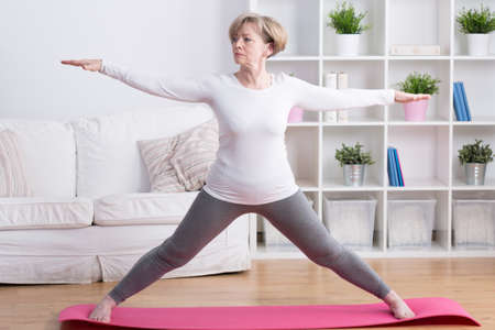 Healthy middle aged woman training yoga at home Stock Photo