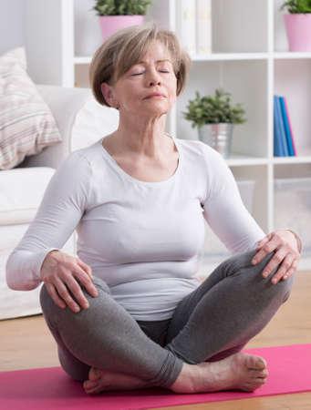 mujer meditando: Mujer madura atractiva entrenamiento de la meditación que hace yoga Foto de archivo
