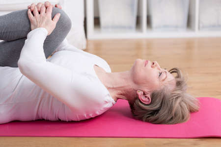 Mature woman training on the exercise floor mat Stock Photo