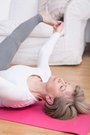 floor mat: Middle aged lady stretching on the floor mat