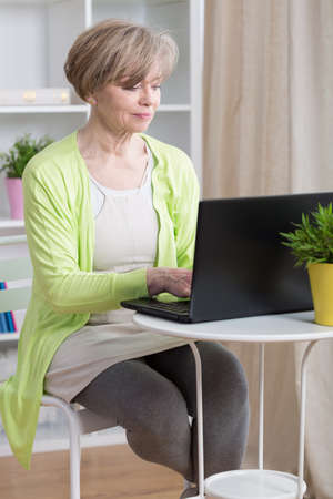 mid adults: Attractive mature woman dating online on laptop