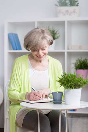 persona escribiendo: Sonriente mujer de mediana edad por escrito en el cuaderno Foto de archivo