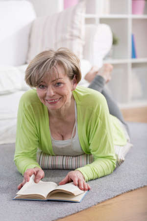 Middle aged lady reading book on the floor photo
