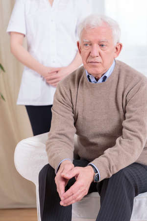 despairing: Despairing sad retiree living in nursing home Stock Photo