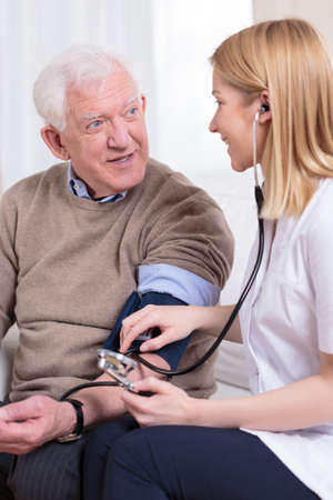 cuff: Nurse measuring blood pressure of senior man Stock Photo