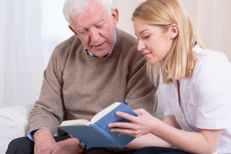 Senior man and caregiver reading interesting book 스톡 콘텐츠
