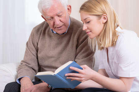 old carer: Senior man and caregiver reading interesting book Stock Photo