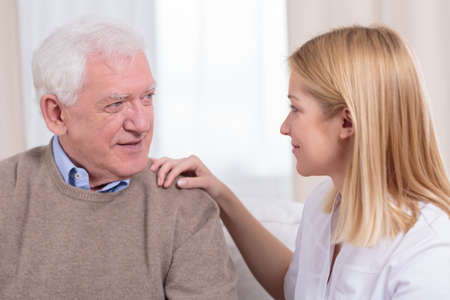 Retiree and senior care assistant talking together
