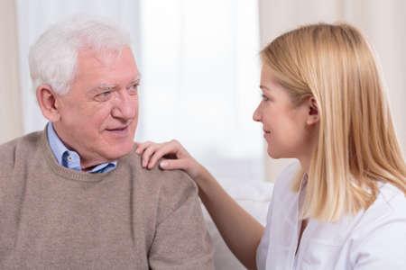 working at home: Jubilados y asistente de cuidado de ancianos hablando juntos